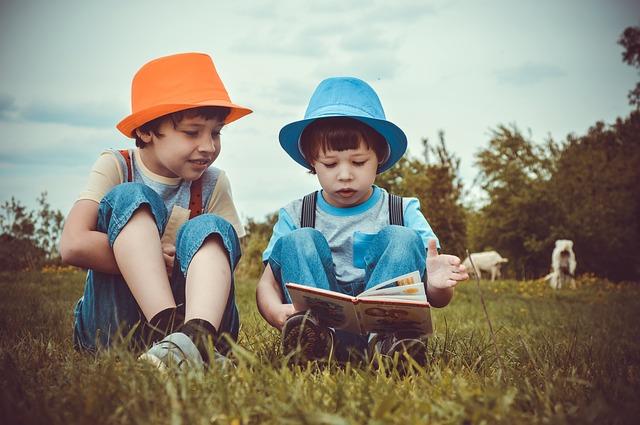 chlapci si venku čtou